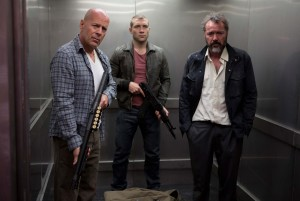 "(l-r) John McClane (Bruce Willis), Jack McClane (Jai Courtney) and a Russian under their protection, Komarov (Sebastian Koch), take a fateful elevator ride in ""A GOOD DAY TO DIE HARD."" ©Frank Masi/20th Century Fox."