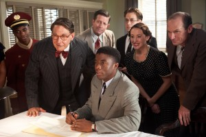 "(Center l-r) HARRISON FORD as Branch Rickey and CHADWICK BOSEMAN as Jackie Robinson, T.R. KNIGHT (standing) as Harold Parrott, RHODA GRIFFIS as Miss Bishop and TOBY HUSS as Clyde Sukeforth in ""42."" ©Warner Bros. Entertainment/Legendary Pictures. CR: D. Stevens."