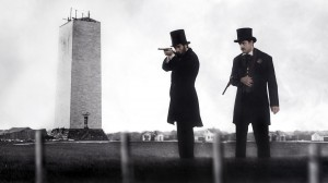 "(l-r) President Abraham Lincoln (Tom Amandes) test fires Spencer rifles with U.S. Marshal Ward Hill Lamon (Lea Coco) in front of the unfinished Washington Monument at the height of the Civil War in ""Saving Lincoln."" ©Saving Lincoln, LLC."