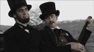 "Ward Hill Lamon (Lea Coco, right) tries to cheer his melancholy friend, President Lincoln (Tom Amandes) with a song in ""Saving LIncoln."" ©Saving Lincoln, LLC."