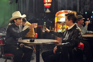 "HANK (Henry Thomas) and SILAS (Jesse James) share a New Year's Eve toast at Dirty John's Bar in ""THE LAST RIDE."" ©Live Bait Productions/Mozark Productions"