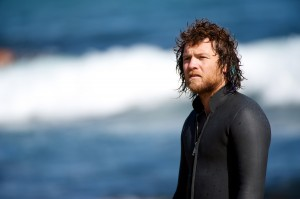 "Sam Worthington stars as JB, a hippie filmmaker/photographer in ""Drift."" ©Lionsgate Entertainment."