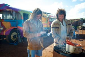 "JB (Sam Worthington, right) prepares a meal on the beach as Jimmy (Xavier Samuel) looks on in ""Drift."" ©Lionsgate Entertainment."