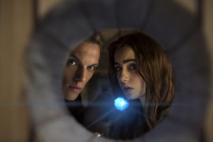 (l-r) Jace (Jamie Campbell Bower) and Clary (Lilly Collins) watch through a bookcase as Pangborn and Blackwell ask Luke where Jocelyn hid the Mortal Cupin Screen Gems fantasy-action THE MORTAL INSTRUMENTS: CITY OF BONES. ©Constantin Film International GmbH and Unique Features (TMI) Inc. CR: Rafy.