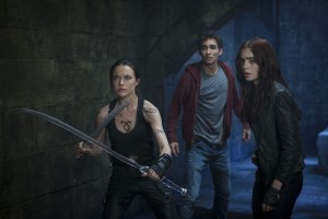 (l-r) Isabelle Lightwood (Jemima West), Simon (Robert Sheehan) and Clary (Lily Collins) prepare to hold off the demons in Screen Gems THE MORTAL INSTRUMENTS: CITY OF BONES. ©Constantin Film International GmbH and Unique Features (TMI) Inc. CR: Rafy.