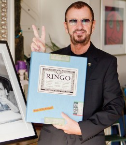 "Ringo Starr takes a photograph with his book ""Photograph, by Ringo Starr."" - ""Photograph, by Ringo Starr, the signed limited edition book of 2,500 copies from www.RingoPhotoBook.com, Tel: +44 (0)1483 540 970, Price $550"""