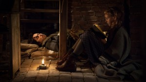 "Liesel (Sophie Nélisse) reads to Max (Ben Schnetzer), who's hiding in her home in ""The Book Thief."" ©20th Century Fox. CR: Jules Heath."