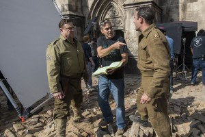 (l to r) John Goodman, director George Clooney and Jean Dujardin on the set of Columbia Pictures' THE MONUMENTS MEN. ©Columbia Pictures. CR: Claudette Barius.