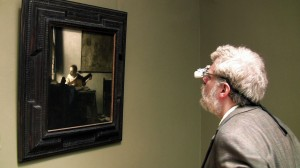 "Tim Jenison, wearing his surgical loupes, inspects Johannes Vermeer's ""Woman with a Lute"" at the Metropolitan Museum of Art in New York in the film TIM'S VERMEER. ©High Delft Pictures. CR: Shane F. Kelly."
