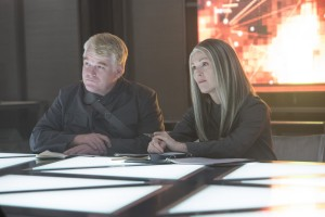 Plutarch Heavensbee (Philip Seymour Hoffman) and President Coin (Julianne Moore) in THE HUNGER GAMES: MOCKINGJAY – PART 1. ©Lionsgate Entertainment. CR: Murray Close.