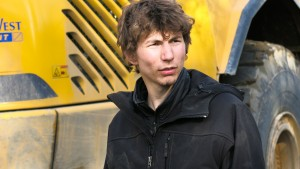 Parker Schnabel in front of a construction vehicle in GOLD RUSH. ©Discovery Channel.
