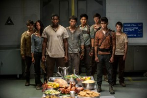 The surviving Gladers react to something they hadn't seen a long time: a feast…courtesy of WCKD.  (left to right) Glader (Gary Hood), Teresa (Kaya Scodelario), Frypan (Dexter Darden), Thomas (Dylan O'Brien), Minho (Ki Hong Lee), Newt (Thomas Brodie-Sangster), Winston (Alexander Flores) and Jack (Bryce Romero) in MAZE RUNNER: THE SCORCH TRIALS. ©20th Century Fox. CR: Richard Foreman, Jr. SMPSP.