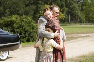 Dalton Trumbo (right, Bryan Cranston) comes home to the embrace of his children, including daughter Niki Tumbo (left, Elle Fanning) in Jay Roach's TRUMBO. ©Bleecker Street. CR: Hilary Bronwyn Gail/Bleecker Street.