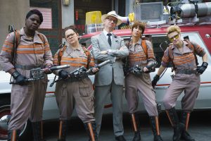 Director Paul Feig poses with the Ghostbusters in front of the Ecto-1.  Patty Tolan (Leslie Jones), Abby Yates (Melissa McCarthy), Erin Gilbert (Kristen Wiig) and Jillian Holtzmann (Kate McKinnon) on the set of Columbia Pictures' GHOSTBUSTERS. ©CTMG. CR: Hopper Stone.
